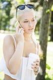 Adolescente con el teléfono y el café en parque Imágenes de archivo libres de regalías