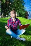 Adolescente con el teléfono y el libro elegantes en parque Fotografía de archivo libre de regalías
