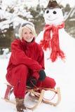 Adolescente con el trineo al lado del muñeco de nieve Fotos de archivo libres de regalías