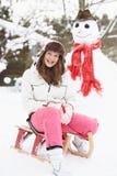 Adolescente con el trineo al lado del muñeco de nieve Foto de archivo