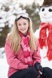 Adolescente con el trineo al lado del muñeco de nieve Fotos de archivo