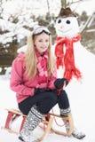 Adolescente con el trineo al lado del muñeco de nieve Imagenes de archivo