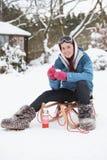 Adolescente con el trineo al lado del muñeco de nieve Fotografía de archivo libre de regalías