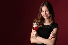 Adolescente con el vino y los brazos cruzados Cierre para arriba Fondo rojo oscuro Fotos de archivo