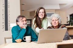 Adolescente con i nonni che per mezzo del computer portatile Fotografia Stock
