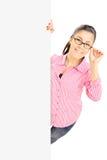 Adolescente con i vetri che stanno dietro il pannello in bianco Fotografia Stock