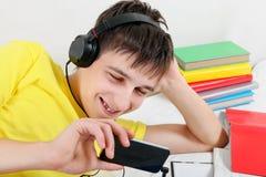 Adolescente con il cellulare ed i libri Immagini Stock