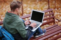 Adolescente con il computer portatile che si siede sul banco nel parco di autunno Immagini Stock