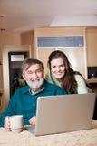 Adolescente con il grandpa che per mezzo del computer portatile immagini stock