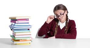 Adolescente con il mucchio dei libri che si siedono alla tavola sul fondo bianco Fotografia Stock