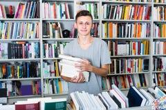 Adolescente con il mucchio del libro in negozio Immagini Stock Libere da Diritti