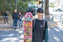 Adolescente con il pattino che attraversa la via fotografia stock libera da diritti