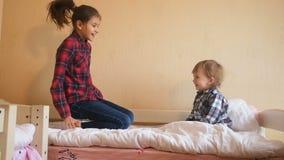 Adolescente con il ragazzo del bambino che ride e che salta sul letto video d archivio