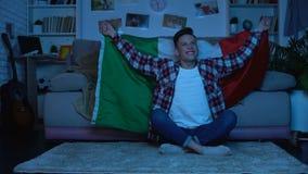Adolescente con la bandiera italiana che incoraggia la casa favorita della squadra di football americano, evento di sport archivi video