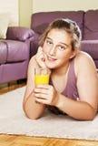 Adolescente con la bebida anaranjada Foto de archivo