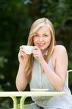 Adolescente con la bebida caliente en el café al aire libre Foto de archivo libre de regalías