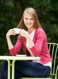 Adolescente con la bebida caliente en el café al aire libre Imagenes de archivo