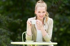 Adolescente con la bebida caliente en el café al aire libre Imágenes de archivo libres de regalías