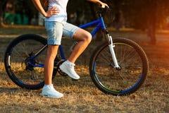 Adolescente con la bici en el parque de la ciudad Imagenes de archivo