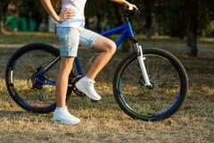 Adolescente con la bici en el parque de la ciudad Foto de archivo libre de regalías
