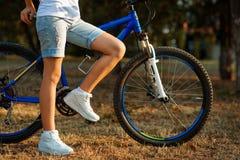 Adolescente con la bici en el parque de la ciudad Fotografía de archivo libre de regalías