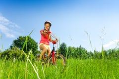 Adolescente con la bicicleta en un prado Fotografía de archivo