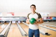 Adolescente con la bola de bolos verde en el callejón Imagen de archivo