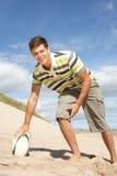 Adolescente con la bola de rugbi en la playa Imagen de archivo