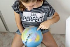 Adolescente con la bola del mundo que busca lugares Fotos de archivo libres de regalías