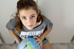 Adolescente con la bola del mundo que busca lugares Fotos de archivo