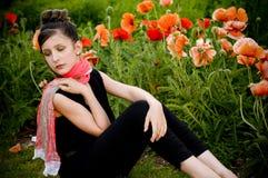 Adolescente con la bufanda roja y las amapolas rojas foto de archivo libre de regalías