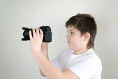 Adolescente con la cámara en luz Imagenes de archivo