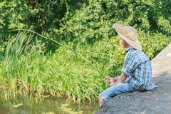 Adolescente con la caña de pescar rústica de madera que pesca con caña en el puente concreto Foto de archivo