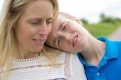 Adolescente con la cabeza del hijo en el hombro Foto de archivo