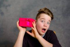 Adolescente con la caja de regalo roja que parece sorprendida Imagen de archivo libre de regalías