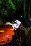 Adolescente con la calabaza en el bosque de Halloween Imagenes de archivo