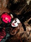 Adolescente con la calabaza en el bosque de Halloween Imagen de archivo
