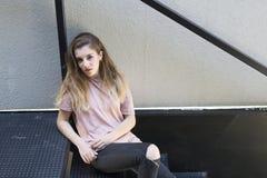 Adolescente con la cara seria que se sienta en una escalera del metal Foto de archivo
