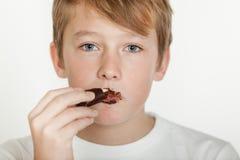 Adolescente con la cara sucia que come el chocolate Fotos de archivo libres de regalías