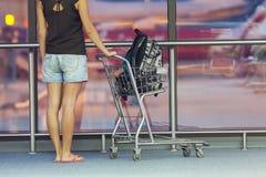 Adolescente con la carretilla en aeropuerto Imágenes de archivo libres de regalías