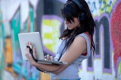 Adolescente con la computadora portátil en yarda de escuela Imagen de archivo libre de regalías