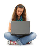 Adolescente con la computadora portátil y el receptor de cabeza Imagen de archivo