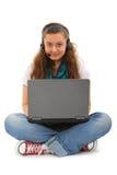 Adolescente con la computadora portátil y el receptor de cabeza Imagenes de archivo