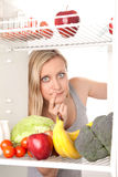 Adolescente con la fruta en refrigerador Imágenes de archivo libres de regalías