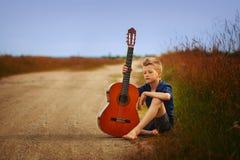 Adolescente con la guitarra acústica en la carretera nacional Fotografía de archivo
