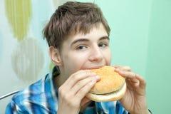 Adolescente con la hamburguesa Fotos de archivo