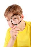 Adolescente con la lente que magnifica Fotografía de archivo libre de regalías