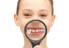 Adolescente con la lupa que muestra los dientes Imagen de archivo libre de regalías