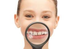 Adolescente con la lupa que muestra los dientes Fotografía de archivo
