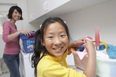 Adolescente con la madre en lavadero Fotos de archivo